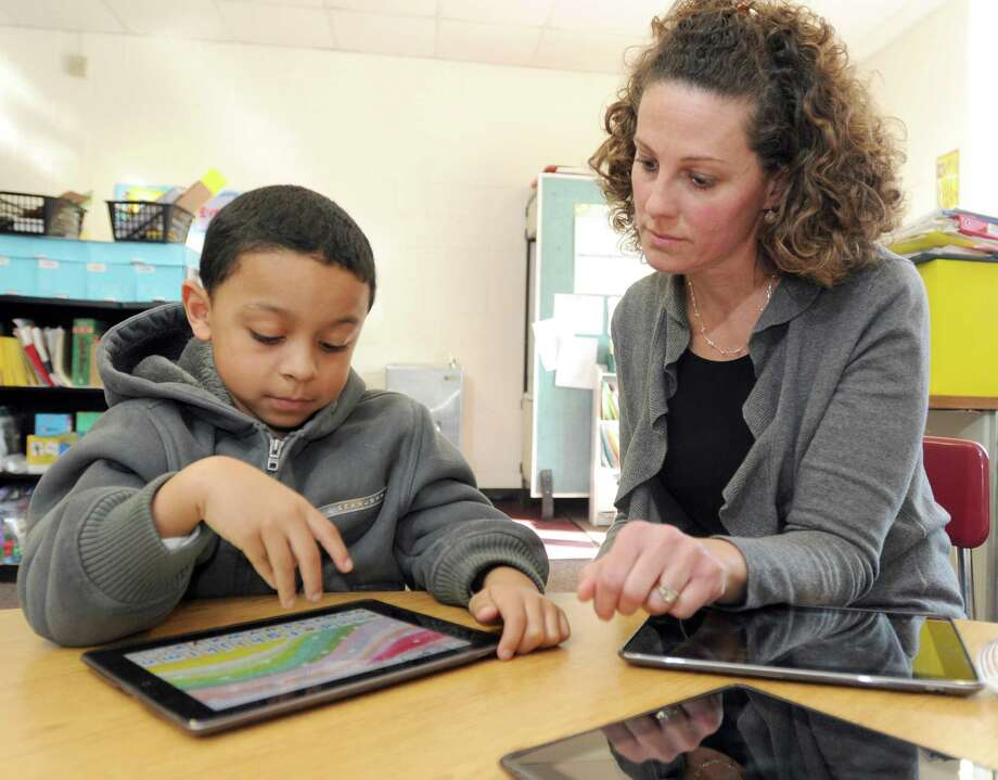 A reading specialist in New Haven, Conn., works with a second-grader. Teachers who believe they should be paid more must think they have the education and skills to merit the increase. They're free to find a new employer who agrees. Photo: Peter Hvizdak / New Haven Register / ©Peter Hvizdak /  New Haven Register