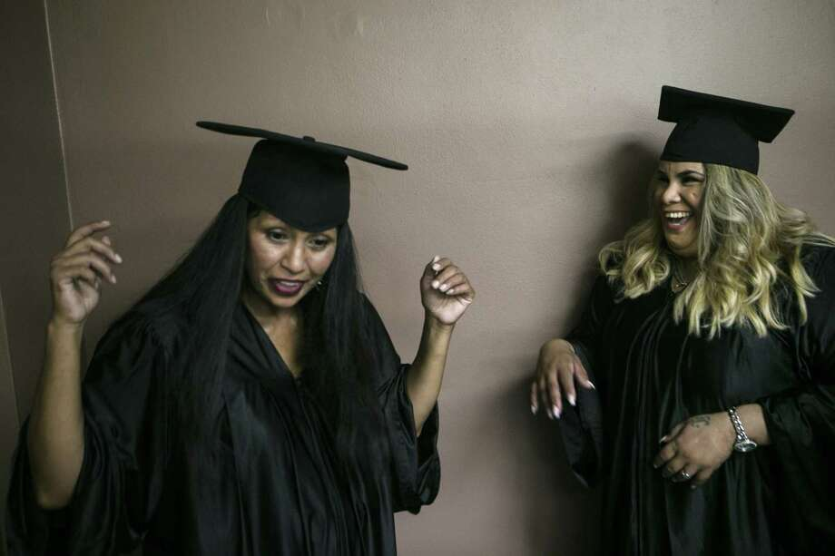 Maria B. has Isabel G. check her cap as Isabel laughs before the third Esperanza Court program graduation held at Crosspoint Chapel in San Antonio Friday, Sept. 28, 2018. The Esperanza Court is a felony specialty court that provides therapy, intensive drug and alcohol treatments and health and social services to participants to address past trauma and abuse and help them move forward. Photo: Josie Norris, Staff / San Antonio Express-News / © San Antonio Express-News