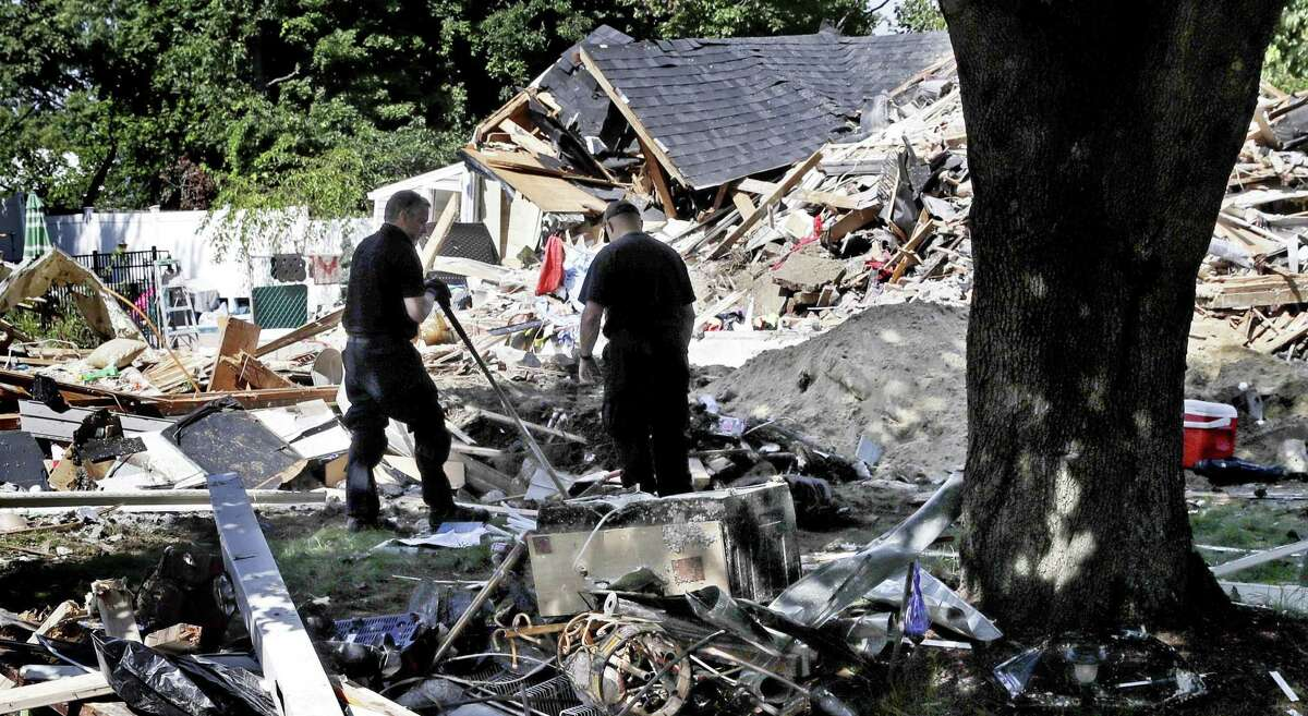 Fire investigators pause while searching the debris at a home which exploded last week following a gas line failure in Lawrence, Mass., Friday, Sept. 21, 2018. Nearly 9,000 homes and businesses may be without gas for weeks as investigators continue to probe what set off the explosions.