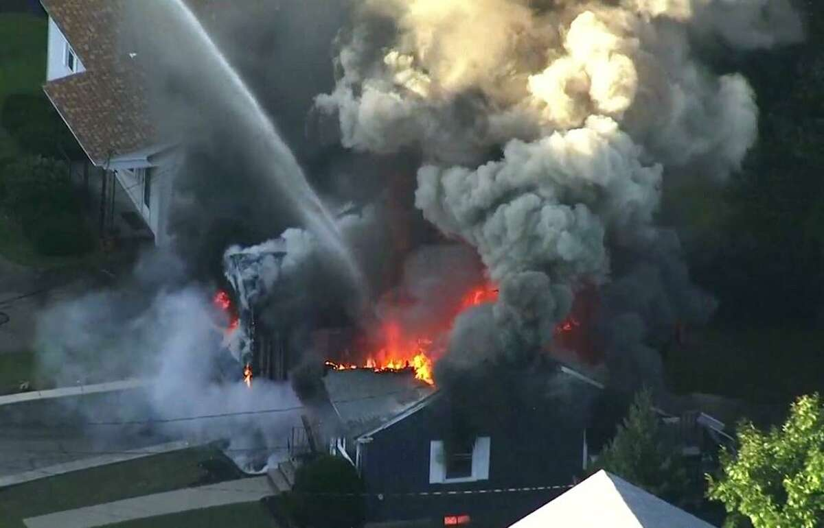 FILE - In this Sept. 13, 2018, file image take from video provided by WCVB in Boston, flames consume the roof of a home in Lawrence, Mass, a suburb of Boston. The pressure in natural gas pipelines prior to a series of explosions and fires in Massachusetts last week was 12 times higher than it should have been. The information was in a letter from the state's U.S. senators to the heads of Columbia Gas and NiSource. (WCVB via AP, File)