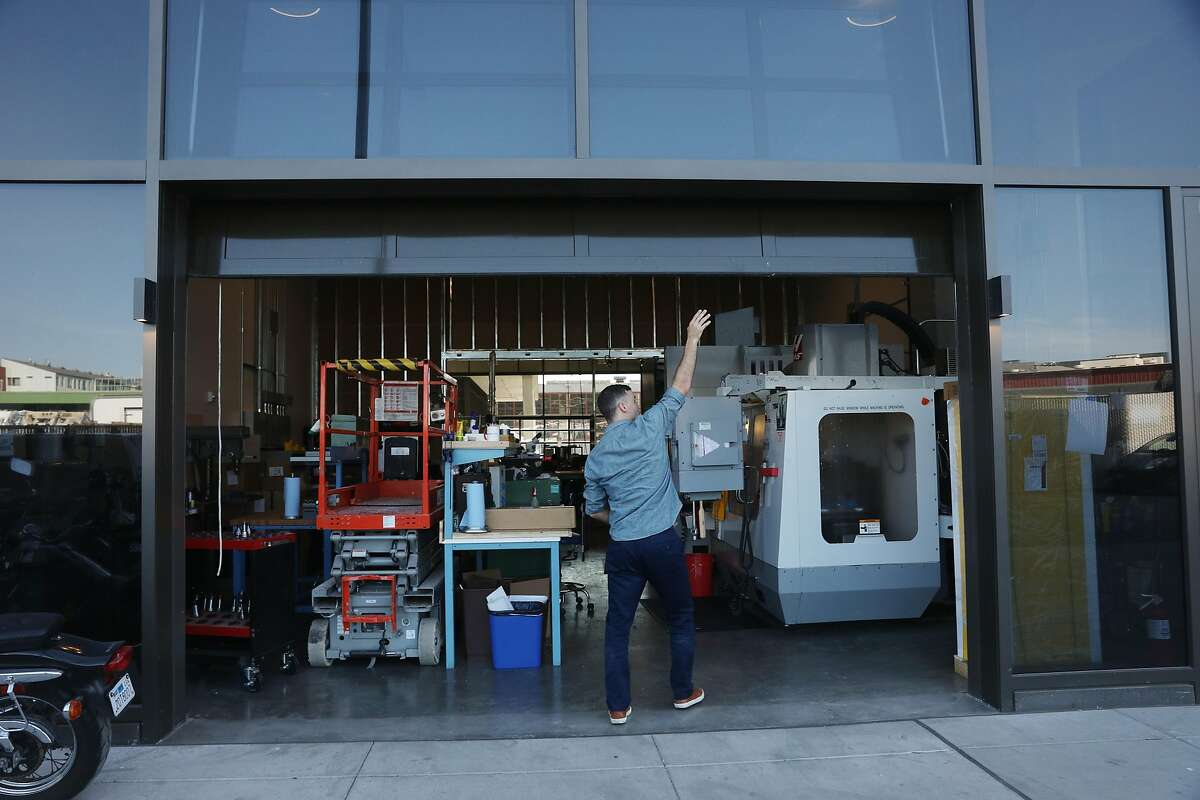 Brett Swope, owner Swope Design Solutions, opens a rolling door onto Channel Street at Swope Design Solutions at 150 Hooper on Friday, October 5, 2018 in San Francisco, Calif.