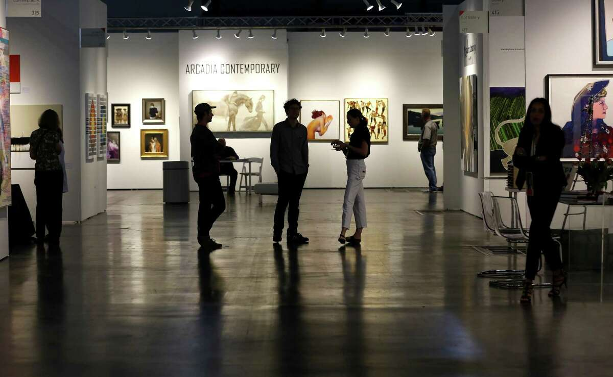 Visitors stroll through the gallery displays during the Texas Contemporary Art Fair at the George R. Brown Convention Center on Friday, Oct. 5, 2018, in downtown Houston.