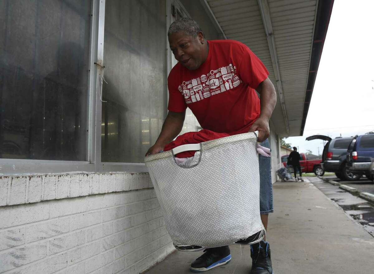 Dallas Mouton picks up a load of dirty laundry to wash at a washateria on Crane Street on Wednesday, Sept. 26, 2018, northeast in Houston. The washateria was the site of a 2016 shooting that police solved with the help of a federal ballistics database.