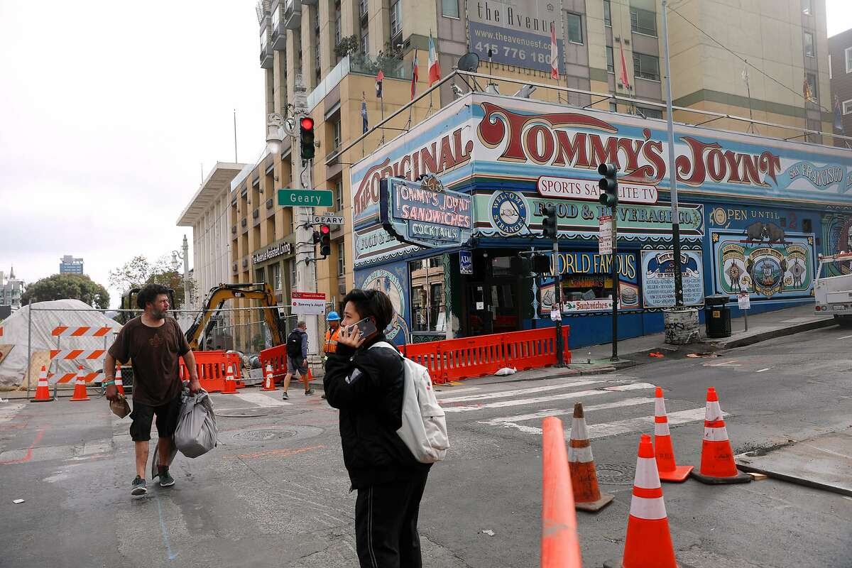 Tommy's Joynt (right background) and equipment for the Van Ness Improvement Project (left background) are seen behind pedestrians crossing Geary Boulevard on Thursday, October 4, 2018 in San Francisco, Calif.