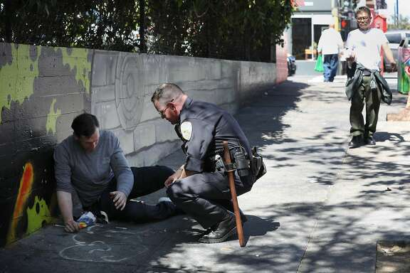 Officer Brian Donohue checks on Jeffrey Choate after he sees him lying on the sidewalk along Larkin Street and asks him to dispose of used needles next to him in a proper container on Monday, September 10,  2018 in San Francisco, Calif.