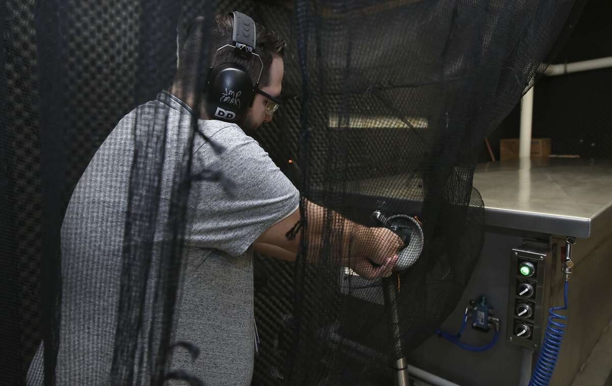 Houston Forensic Science Center National Integrated Ballistics Information Technician Joseph Parian shoots into a water tank as a demonstration in a lab located in Houston Police Department Headquarters building on Monday, Sept. 24, 2018, in Houston. HFSC recently brought a proposal to Houston City Council to move out of it and into another building downtown.