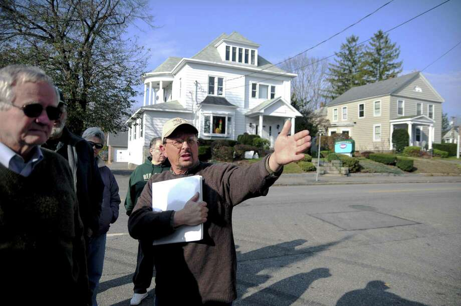 Mark McEachern, executive director of the Torrington Historical Society leads a tour of the downtown's historic buildings in 2012. To right is the oldest building in the downtown district, the house at 241 Main St., which was built between 1882 and 1883. After many years of service, Dr. David R. Bennett has retired as President of the Board of Directors of the Torrington Historical Society and has been succeeded in that position by John E. Janco. Photo: Alec Johnson / Associated Press / Republican-American