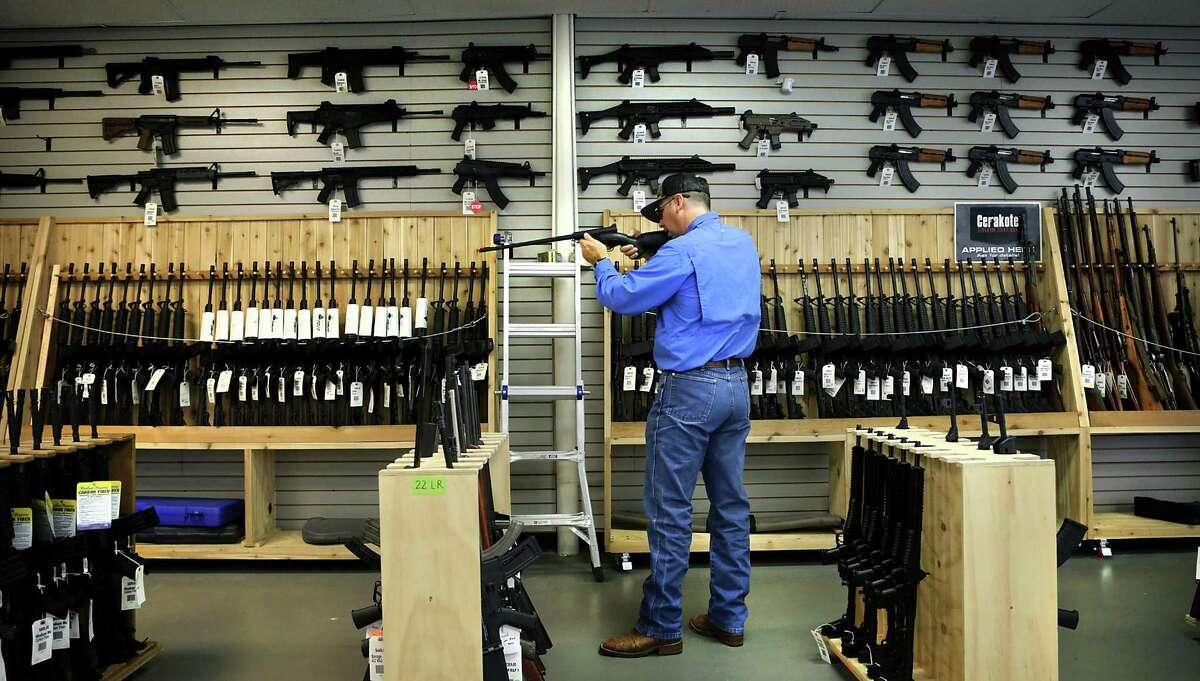 In 2016, a customer inspects a rifle at Adelbridge & Co. Firearms.