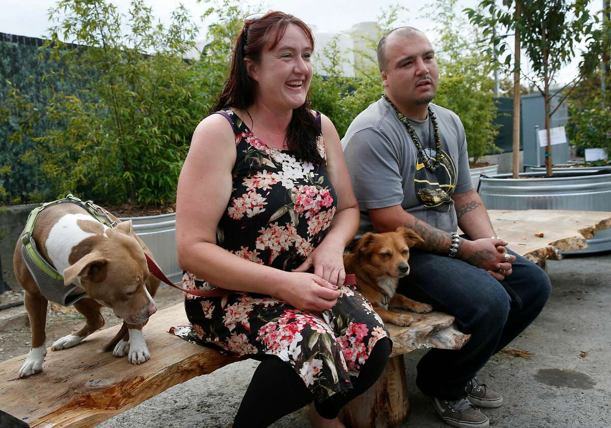 Sarah Smith and her boyfriend Zack Minjarez, with their dogs Bella and Buddha, are preparing to move out of the Pathways STAIR Center temporary housing community in Berkeley, Calif. on Wednesday, Oct. 3, 2018. The couple, who have been staying at the shelter for several weeks, are moving into an East Oakland studio apartment later in the day.
