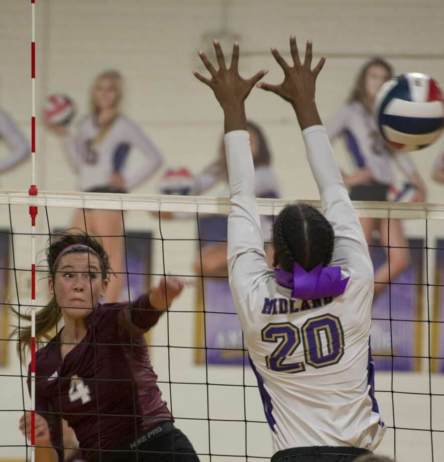 Lee's McKenzie Gibson hits the ball past the arms of Midland High's Aniya Clinton 10/05/18 in the cross-town match at MHS gym. Tim Fischer/Reporter-Telegram Photo: Tim Fischer/Midland Reporter-Telegram