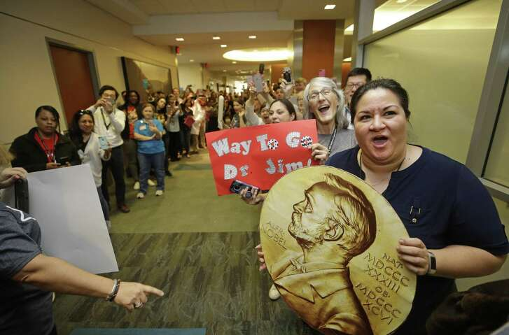 People line up to cheer for Jim Allison at MD Anderson Cancer Center Friday in Houston as part of a celebration of his receiving the Nobel Prize earlier this week.