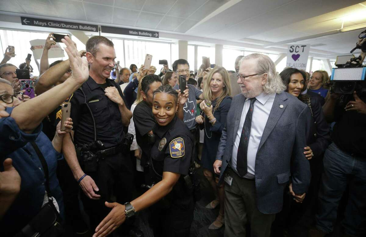 Security helps Jim Allison and his wife, Pam Sharma, walk through a procession at MD Anderson Cancer Center Friday, Oct. 5, 2018, in Houston as part of a celebration of his receiving the Nobel Prize earlier this week.