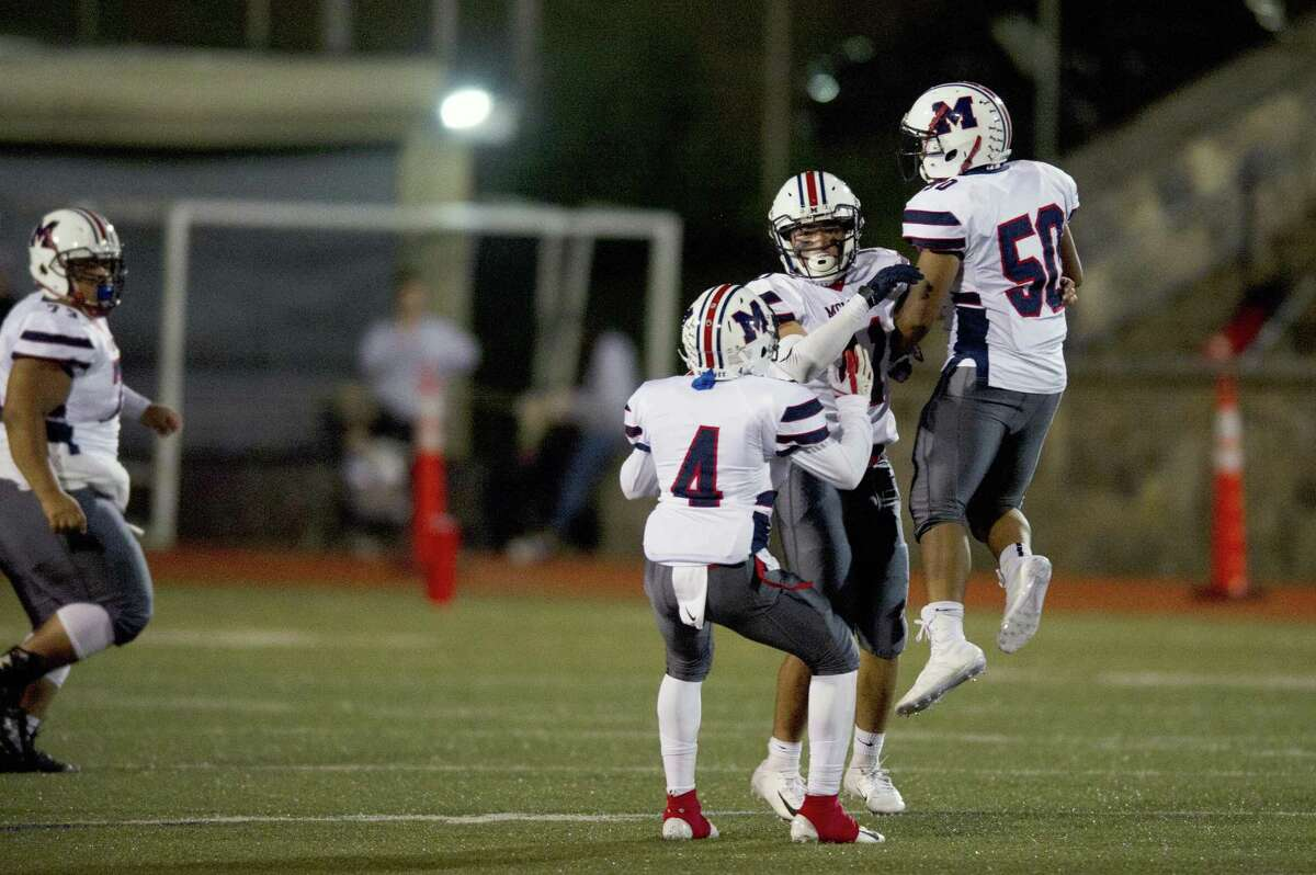 Brien McMahon High School seniors Donyae Shavers (4) and Neno Brown (50) celebrate with Jonathan Davilla after a crucial third down sack during a varsity football game against Stamford High School at Boyle Stadium in Stamford, Conn. on Friday, Oct. 5, 2018.