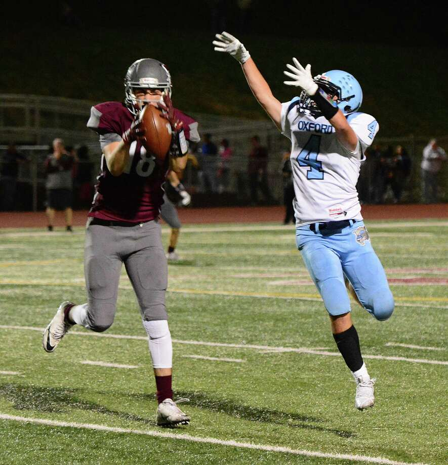Naugatuck's Ty Coney, left, steps in front of Oxford's Johnny Biondo to notch an interception during Friday's game at Veterans Field in Naugatuck. The host Greyhounds won 49-7. Photo: John Nash / Hearst Connecticut Media