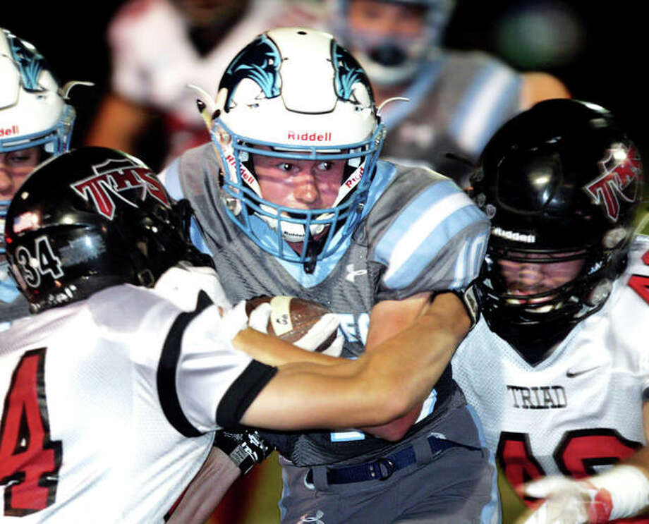 Jersey's Will Medford looks for extra yardage as he tries to push past Triad's Geno Riggar during a first half punt return Friday in Jerseyville. Photo: James B. Ritter | For The Telegraph