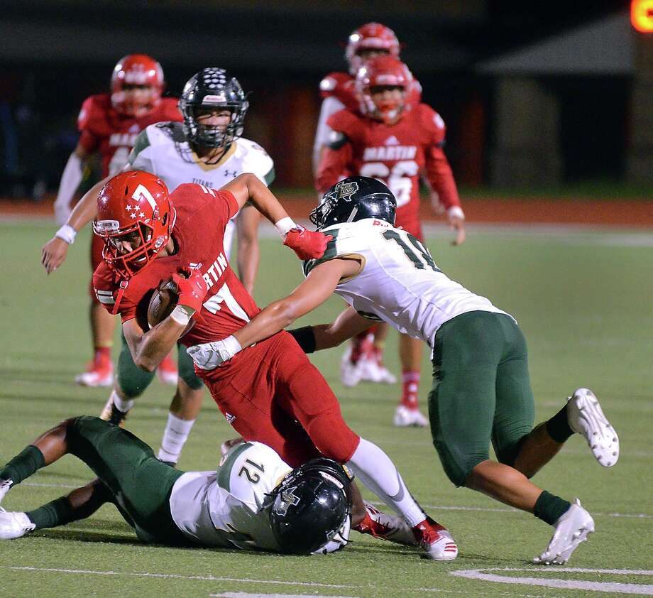 Wide receiver Miguel Sanchez is tackled by a pair of defenders as the Martin Tigers and San Antonio Southwest Legacy played Friday, October 5, 2018 at Shirley Field. Photo: Cuate Santos / Laredo Morning Times / Laredo Morning Times