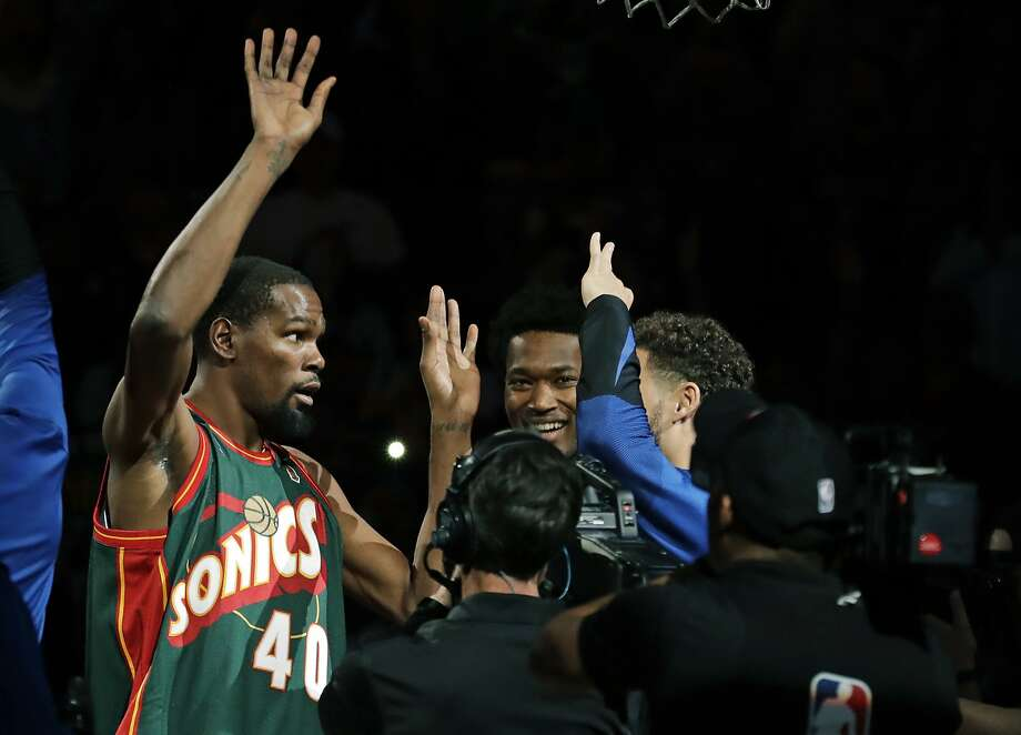 Golden State Warriors forward Kevin Durant, left, appears during player introductions wearing the jersey of Seattle SuperSonics great Shawn Kemp as he greets teammates before an NBA basketball preseason game against the Sacramento Kings, Friday, Oct. 5, 2018, in Seattle.  Photo: Ted S. Warren / Associated Press