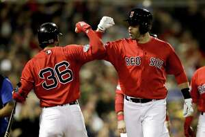 J.D. Martinez of the Red Sox celebrates after his three-run home run with Eduardo Nunez during the first inning of Game 1 of the ALDS. (AP Photo/Charles Krupa)