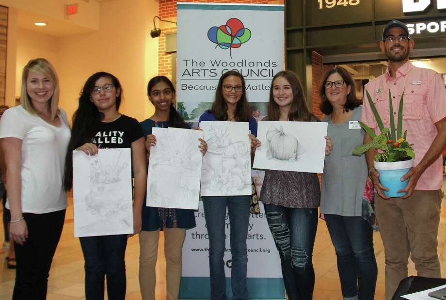 Students from the 6th Annual Fast Draw Competition sponsored by The Woodlands Arts Council display their award-winning work. Pictured from left are: TWAC Outreach Coordinator Chloe Snow, Karla Hernandez, Roopa Pabolu, Natalie Sorber, Marlie Thompson, TWAC Board President Deb Spiess and Leo Brito, owner of Woodlands Escapes. Photo: Courtesy Of The Woodlands Arts Council / Courtesy Of The Woodlands Arts Council