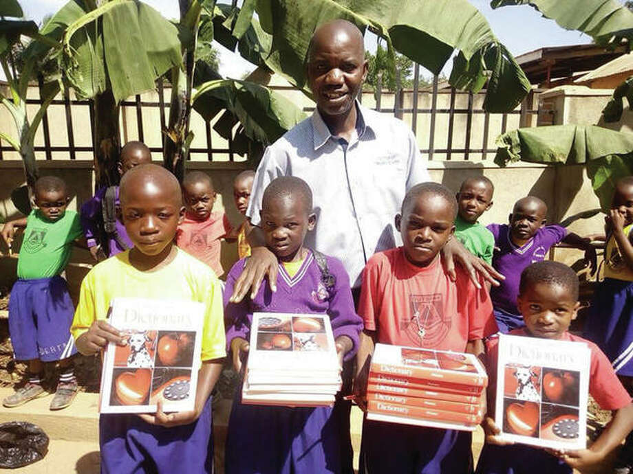 Students at the Nabitalo Senior Secondary School in Uganda show off some of the dictionaries they received through Project Restore and Edwardsville District 7. Photo: For The Intelligencer