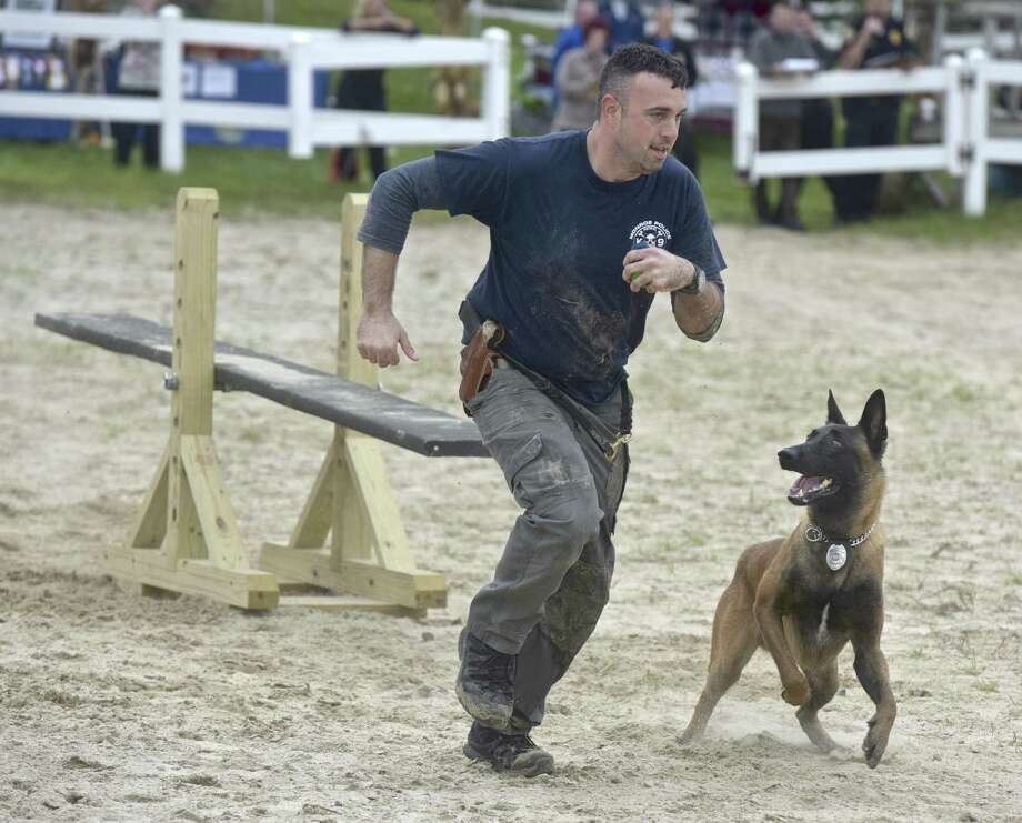 Monroe Police Officer Jeff Loomis, runs the obstacle course with Riggs during the 4th Annual 2018 Western Connecticut police K-9 Challenge. Saturday, October 6, 2018, at the 2nd Company Governor's Horse Guard, Newtown, Conn. Photo: H John Voorhees III / Hearst Connecticut Media / The News-Times
