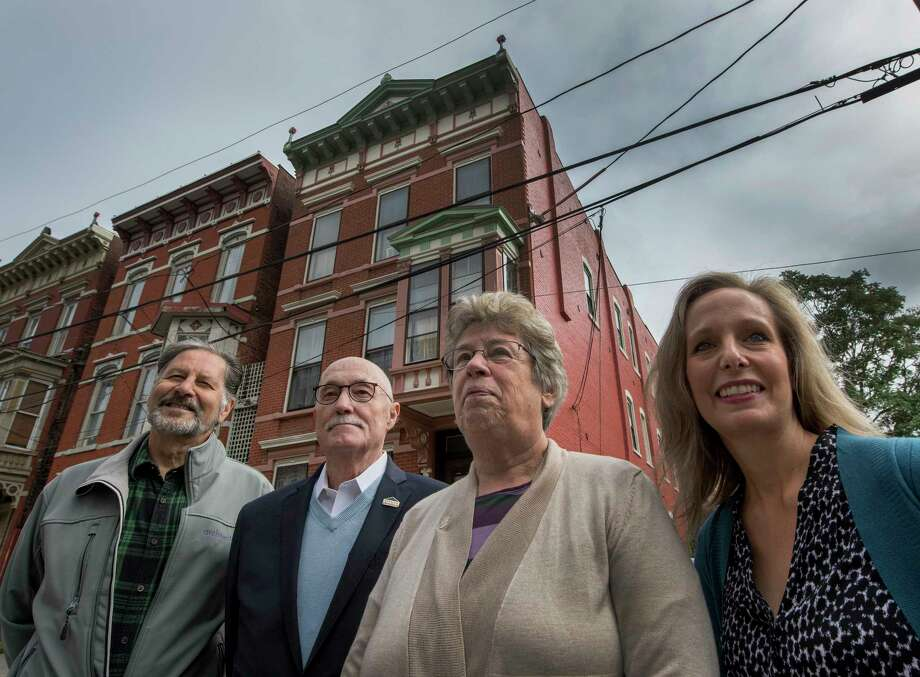 Four former and present executive directors of TRIP stand in front of a row houses on Old 6th Avenue Wednesday Oct. 3, 2018 in Troy, N.Y. Former executive directors are from left;  Vinny Lepera, Duncan Barrett,and Barbara Jones Higbee and the present executive director Christine Nealon stand to the right of the former directors.  (Skip Dickstein/Times Union) Photo: SKIP DICKSTEIN / 200449904A