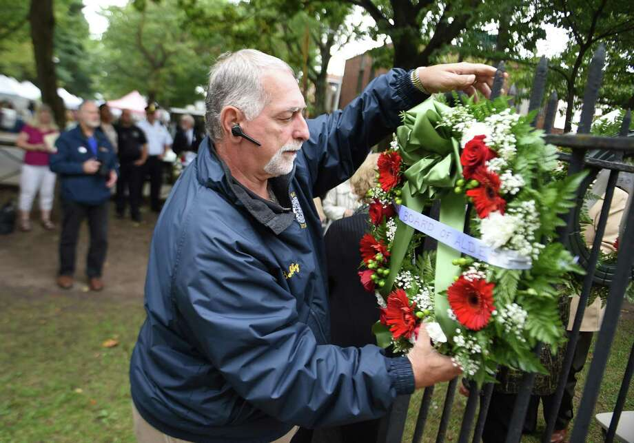 Bobby Parente of East Haven hangs wreaths on a fence surrounding a statue of Christopher Columbus during the Greater New Haven Columbus Day Committee's Annual Wreath Presentation Ceremony in New Haven's Wooster Square on October 6, 2018. Photo: Arnold Gold / Hearst Connecticut Media / New Haven Register