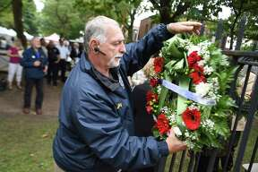 Bobby Parente of East Haven hangs wreaths on a fence surrounding a statue of Christopher Columbus during the Greater New Haven Columbus Day Committee's Annual Wreath Presentation Ceremony in New Haven's Wooster Square on October 6, 2018.