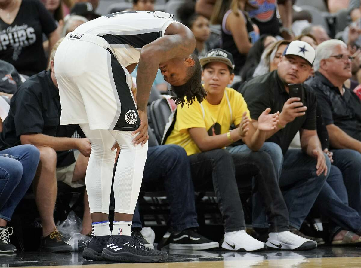 San Antonio Spurs' Lonnie Walker IV pauses on the court after injuring his leg during the second half of an NBA preseason basketball game against the Detroit Pistons, Friday, Oct. 5, 2018, in San Antonio. San Antonio won 117-93. (AP Photo/Darren Abate)
