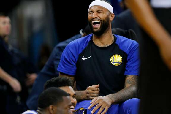 Golden State Warriors center DeMarcus Cousins (0) has a laugh with his teammates on the bench during the second half of an NBA preseason game between the Golden State Warriors and Minnesota Timberwolves at Oracle Arena on Saturday, Sept. 29, 2018, in Oakland, Calif. The Minnesota Timberwolves won 114-110.