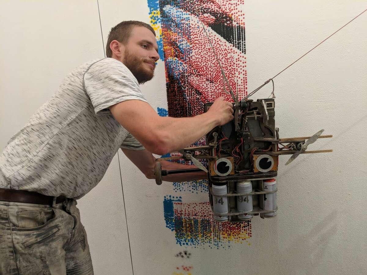 Mihkel Joala fixes Albert, a robot that paints murals, during a test print.