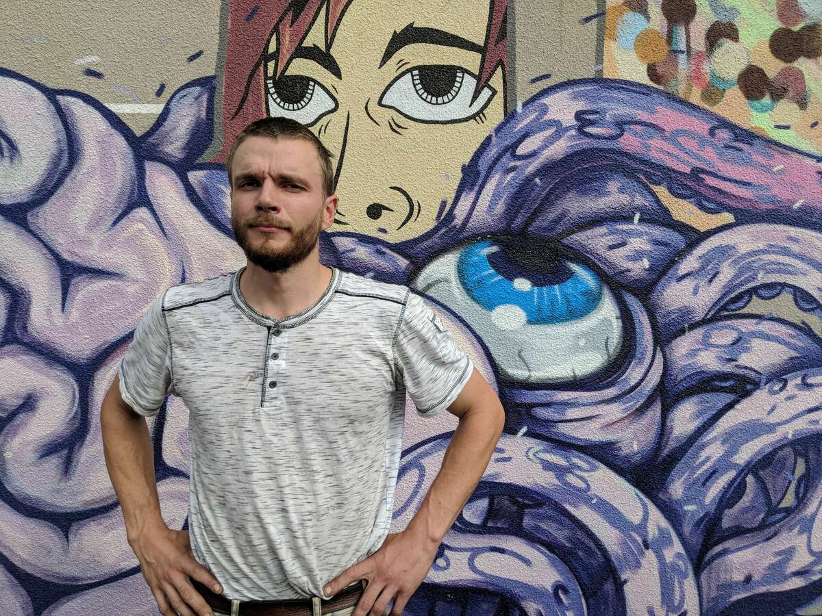 Mihkel Joala, the inventor of the mural painting robot Albert, stands in front of a mural in San Francisco.