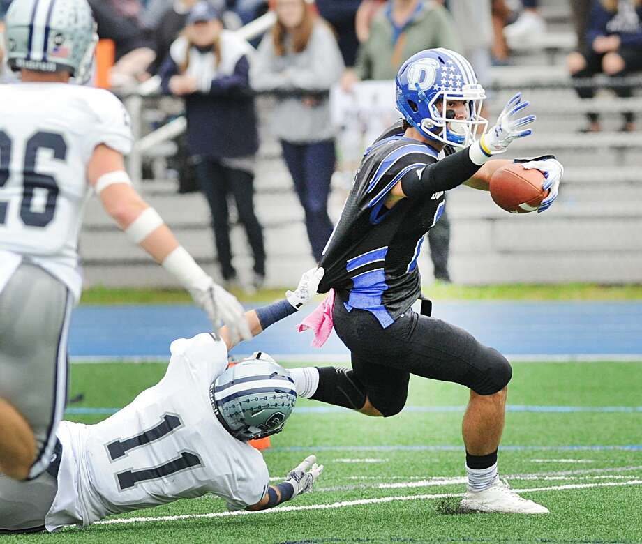 Staples defender Kevin Rabacs (#11), left, attempts to tackle Darien receiver William Rolapp during the high school football game between Darien High School and Staples High School at Darien, Conn., Saturday, Oct. 6, 2018. Darien shutout Staples winning the game, 24-0. Photo: Bob Luckey Jr. / Hearst Connecticut Media / Greenwich Time