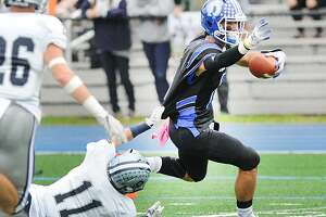 Staples defender Kevin Rabacs (#11), left, attempts to tackle Darien receiver William Rolapp during the high school football game between Darien High School and Staples High School at Darien, Conn., Saturday, Oct. 6, 2018. Darien shutout Staples winning the game, 24-0.