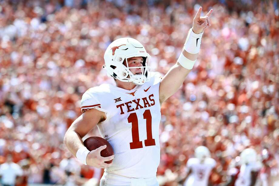"Texas quarterback Sam Ehlinger flashes the ""hook 'Em Horns"" sign after scoring a rushing touchdown against Oklahoma at the Cotton Bowl. Photo: Tom Pennington / Getty Images"