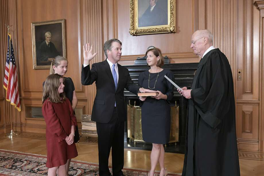 WASHINGTON, DC - OCTOBER 6: In this handout photo provided by the Supreme Court of the United States, Justice Anthony M. Kennedy, (Retired) administers the Judicial Oath to Judge Brett M. Kavanaugh as his wife Ashley Kavanaugh holds the Bible while joined by their daughters Margaret and Liza, in the Justices Conference Room at the Supreme Court Building on October 6, 2018 in Washington, DC.  (Photo by Fred Schilling/Supreme Court of the United States via Getty Images) Photo: Handout, Getty Images