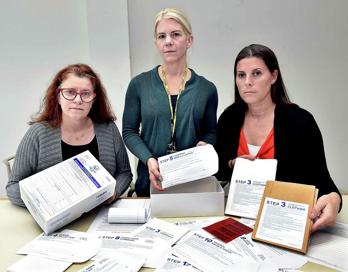 Laura Cordes, director of the CT Alliance, Cheryl Carreiro, laboratory quality assurance manager and Kristin Sasinouski, deputy director of forensic biology and DNA display the contents of the State of Connecticut Sexual Assault Evidence Collection Kit at the State Crime Lab in Meriden Wednesday, Sept. 26.
