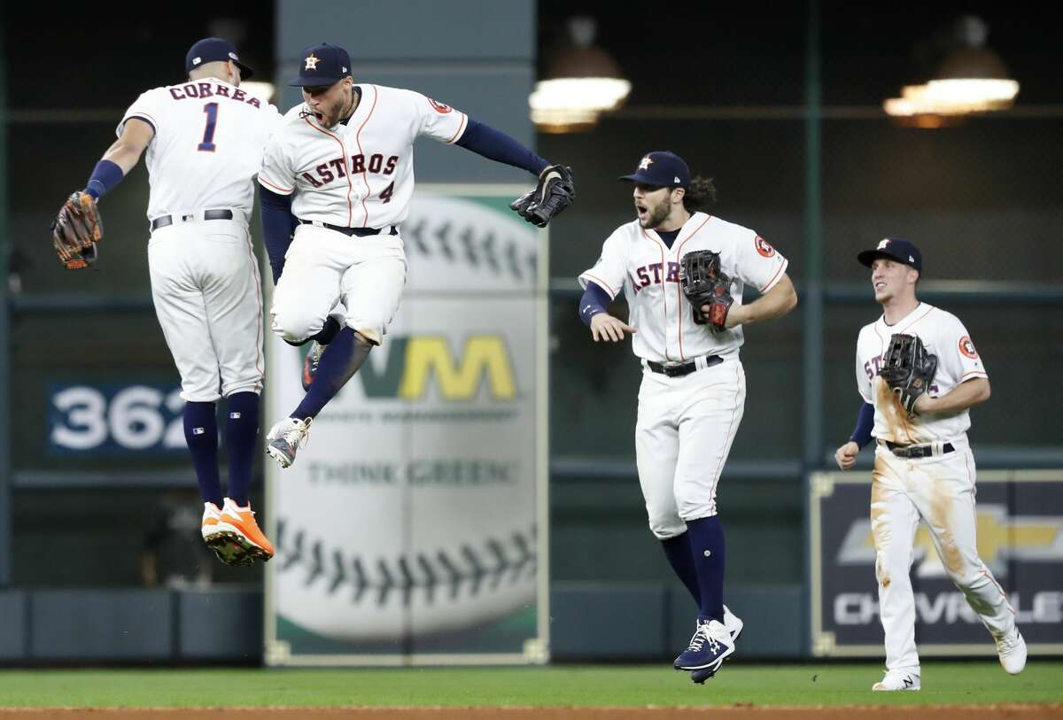 Houston Astros shortstop Carlos Correa (1), Houston Astros outfielder George Springer (4), Houston Astros outfielder Jake Marisnick (6) and Houston Astros Myles Straw (26) celebrate the win in Game 2 of the American League Division Series at Minute Maid Park on Saturday, Oct. 6, 2018, in Houston.