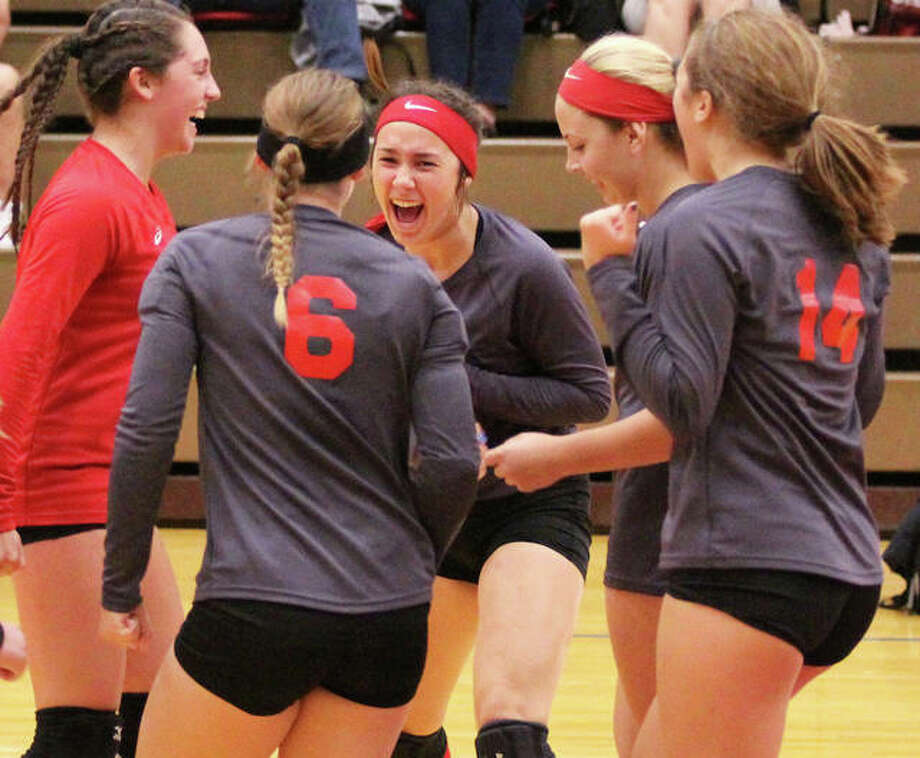 Staunton's (from left) Hollie Bekeske, Sarah Isenberg (6), Gabbie Reising, Savannah Billings and Katie Masinelli celebrate a point that put the Bulldogs one point away from a third-set victory in the title match of the Macoupin County Tournament on Saturday in Carlinville. Photo: Greg Shashack / The Telegraph