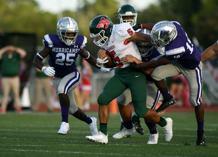 The Woodlands junior running back Bryeton Gilford, center, drags three Klein Cain defenders in the first quarter of a District 15-6A matchup at Klein Memorial Stadium on Saturday, Oct. 6, 2018. Photo: Jerry Baker, Houston Chronicle / Contributor / Houston Chronicle