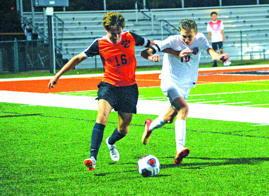Edwardsville's Josh Reed, left, and Alton's Jake Lombardi battle for the ball during the second half of Saturday's game at the District 7 Sports Complex. Photo: Scott Marion