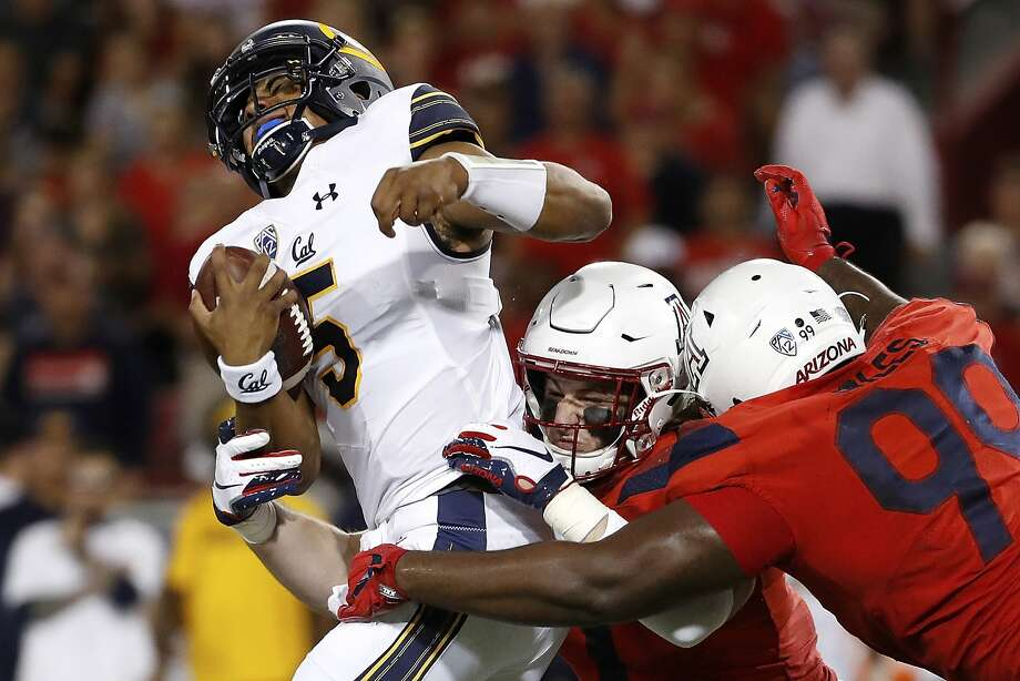 Arizona linebacker Colin Schooler (7) and defensive tackle Dereck Boles (99) tackle California quarterback Brandon McIlwain (5) during the first half of an NCAA college football game Saturday, Oct. 6, 2018, in Tucson, Ariz. (AP Photo/Chris Coduto) Photo: Chris Coduto / Associated Press