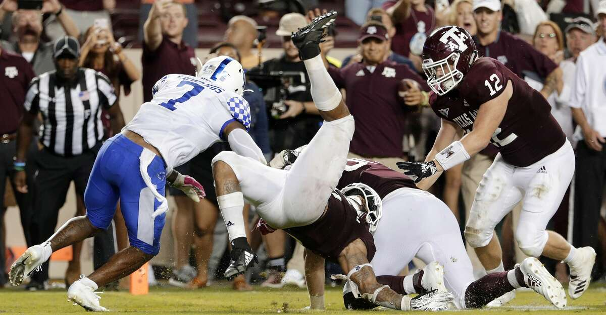 Texas A&M running back Trayveon Williams (5) dives over tight end Trevor Wood to score and win an NCAA college football game as fullback Cullen Gillaspia (12) follows and Kentucky safety Mike Edwards (7) defends in overtime Saturday, Oct. 6, 2018, in College Station, Texas. (AP Photo/Michael Wyke)