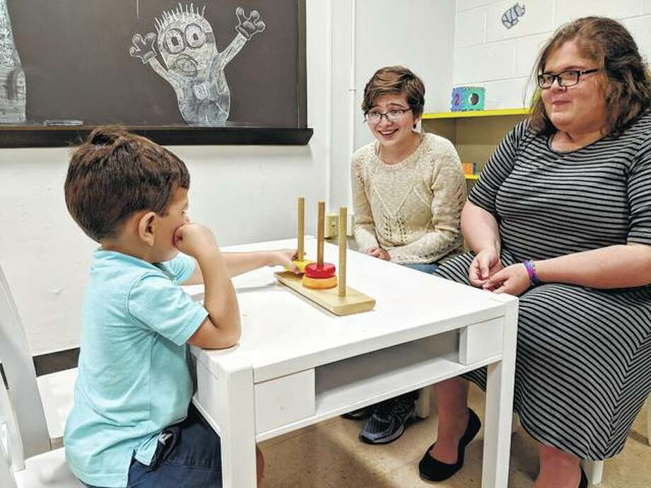Illinois College students Emily Benca (left) and Samantha MacFarland play a game with a 3-year-old boy in the college's observation room at the psychology department.