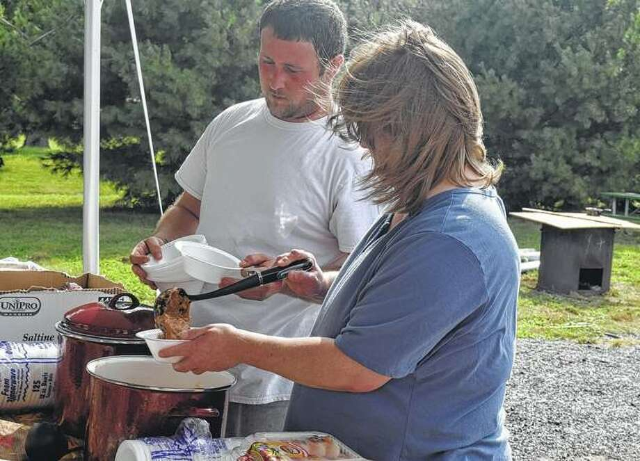 Dawn Surratt and Josh Hayes serve burgoo Saturday during the South Jacksonville Celebration.