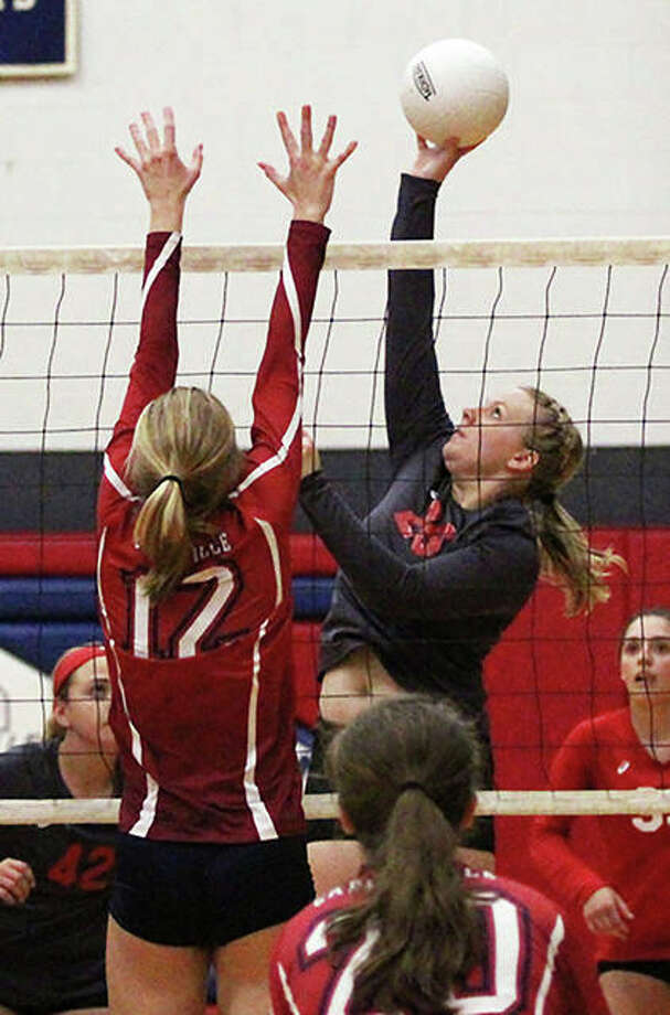 Staunton's Ashleigh Painter (right) tips over the block of Carlinville's Adriann Welte (12) during the championship match of the Macoupin County Tournament on Saturday at Carlinville. Staunton won in three sets to repeat as county champion. Photo: Greg Shashack / The Telegraph