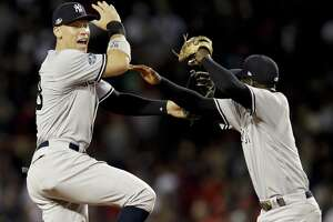Yankees right fielder Aaron Judge (left) celebrates with center fielder Andrew McCutchen after a 6-2 win over the Red Sox in Game 2 of the ALDS Saturday in Boston. (AP Photo/Charles Krupa)