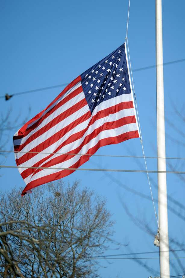 The large flag at the main intersection in Newtown, Conn. remains at half staff Dec. 20th, 2012, in honor of the twenty students killed in the mass shooting at Sandy Hook Elementary School last Friday. Photo: Ned Gerard / Ned Gerard / Connecticut Post
