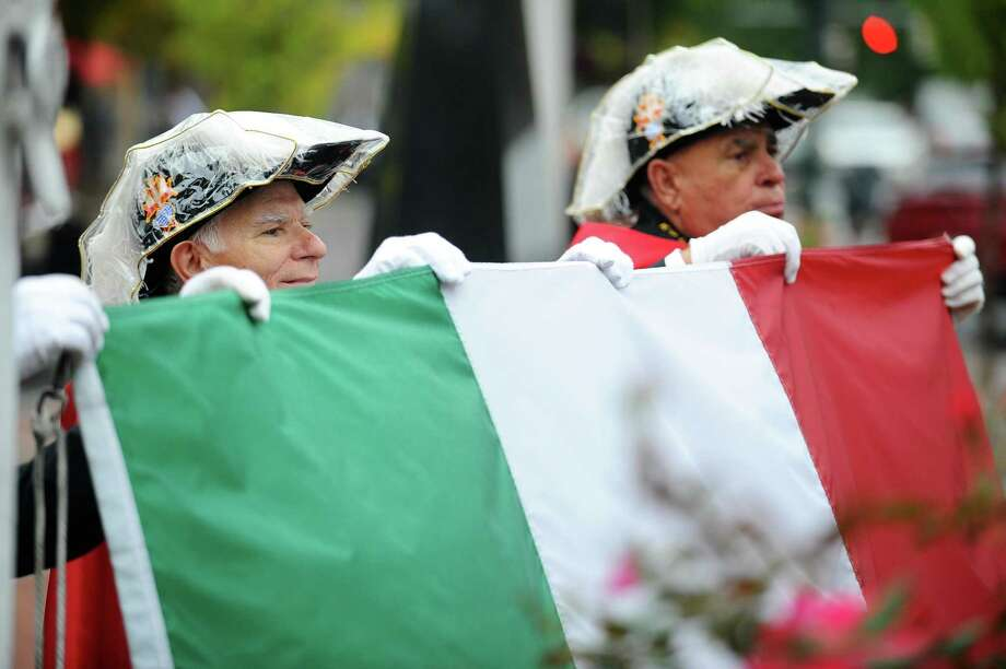 Frank Leone, left, and Joe Rainone hold the Italian flag after the flagpole rope fell off during the Columbus Day Italian Street Festival in Columbus Park in downtown Stamford, Conn. on Sunday, Oct. 8, 2017. Photo: Michael Cummo / Hearst Connecticut Media / Stamford Advocate