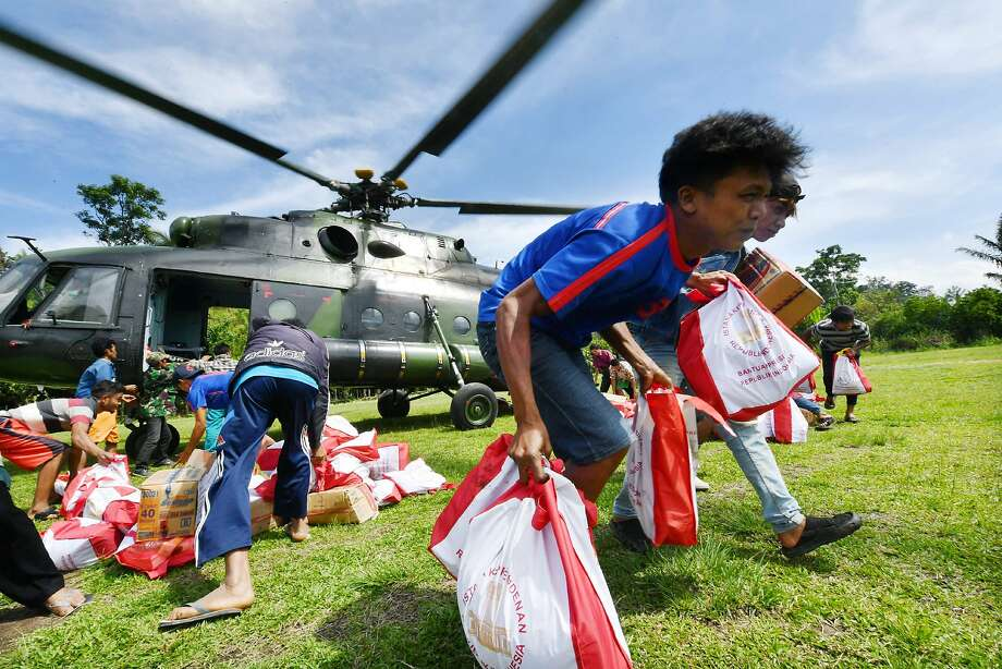 Residents unload relief supplies from a military helicopter in the village of Proo. Search operations are expected to end by Thursday, nearly two weeks after the 7.5 earthquake struck. Photo: Adek Berry / AFP / Getty Images